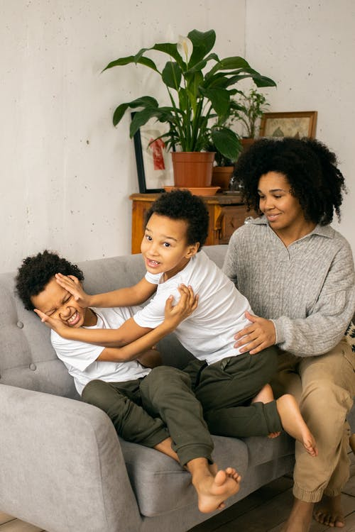 Cheerful African American mother sitting on sofa near cute barefoot black sons having fun while playing together in light room