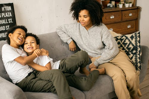 Cheerful African American boys in casual wear hugging on comfortable sofa with caring black mother in light room with wooden cupboard