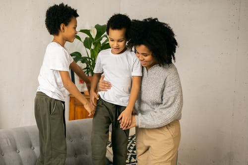 Cheerful black sons standing on couch near mother