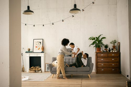 Full body of African American mother standing near sons having fun on sofa in light room with fireplace and hanging garland