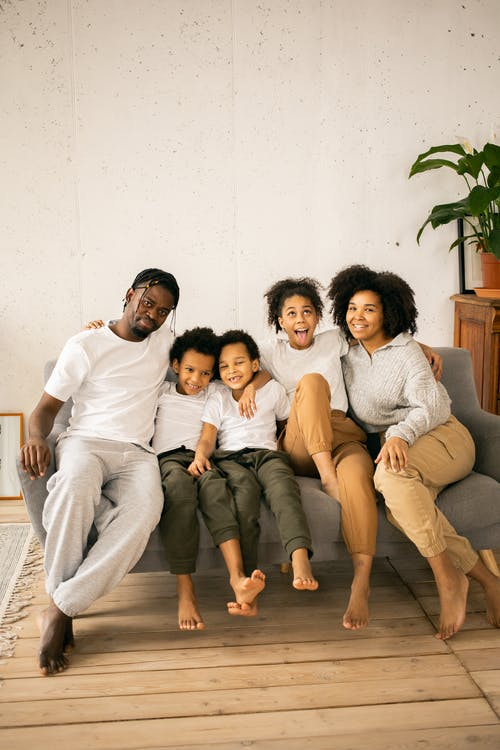 Joyful black family sitting together on couch in room