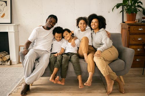 Full body of cheerful African American parents with children looking at camera while sitting on sofa in room with fireplace