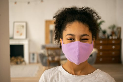 Cheerful African American teenage girl wearing protective mask winking and looking at camera on blurred background during coronavirus pandemic at home