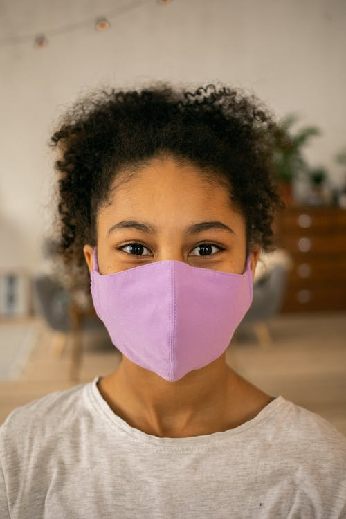 Content African American teenage girl in purple protective mask looking at camera in room against blurred background during coronavirus pandemic
