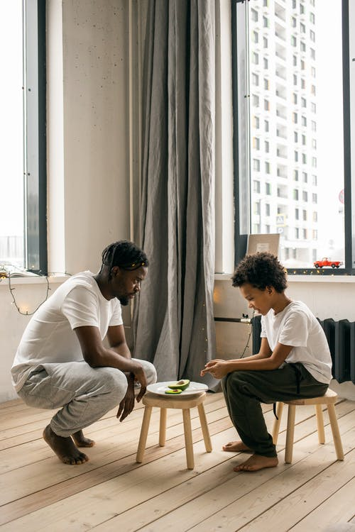 Black father with son near plate with avocado in room