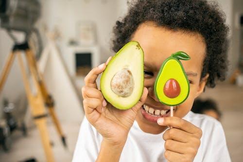 Happy black boy with avocado and lollipop
