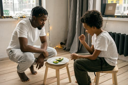 Black man with son near plate with avocado and similar lollipop