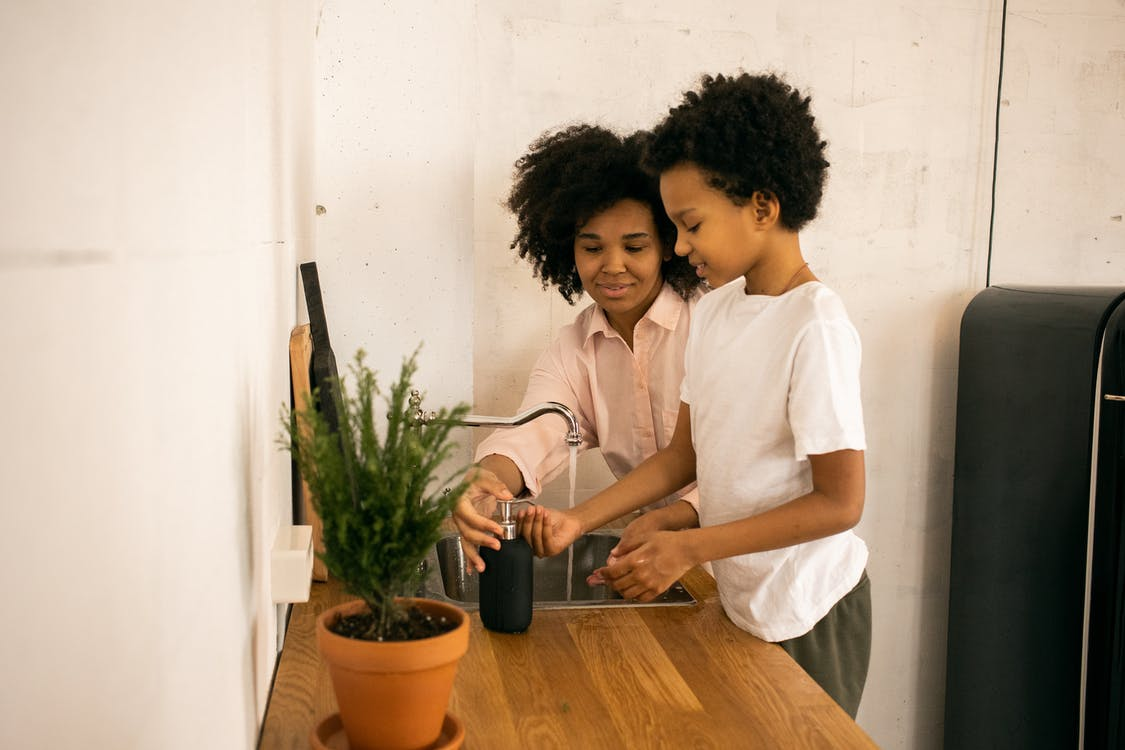 Glad African American mother with son applying soap on hands while washing hands near counter with green potted plant at home