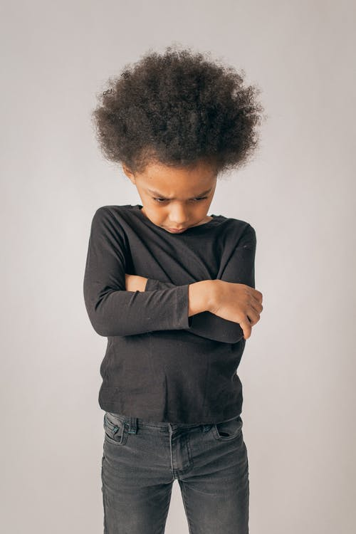Sad African American girl with Afro hairstyle and black outfit standing with crossed arms on white background in light studio