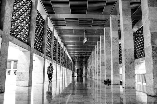 Grayscale Photo of People Walking on Hallway