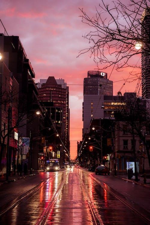 Road between buildings on dark street