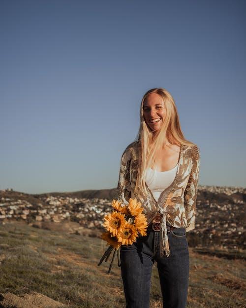 Woman in White Long Sleeve Shirt Holding Sunflower