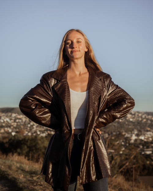 Woman in Brown Leather Jacket Standing on Brown Grass Field
