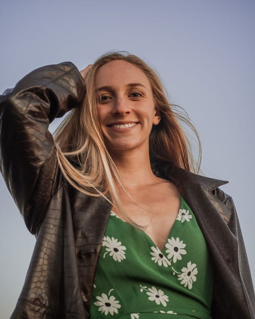 Woman in Green and White Floral Shirt and Black Leather Jacket Smiling