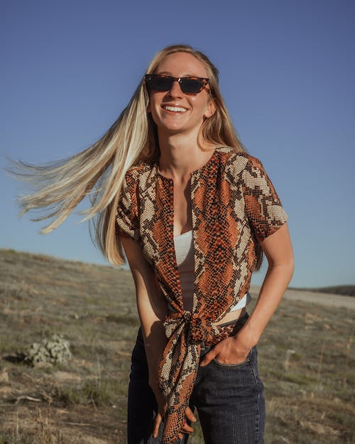 Woman in Brown and White Floral Shirt and Blue Denim Jeans