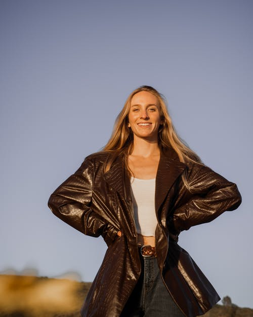 Woman in Brown Leather Jacket Standing on Brown Field