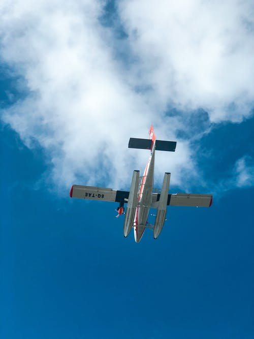 Red and White Light Aircraft Flying Under Blue Sky
