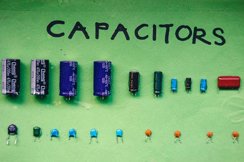 Top view layout of various capacitors for storing electrical energy of different sizes and capacities arranged on green background with inscription