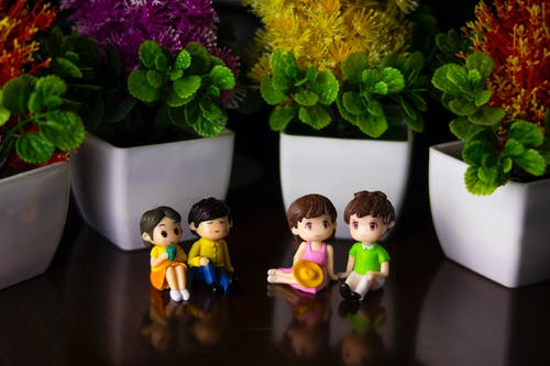 Couples of figurines on table near flowerpots