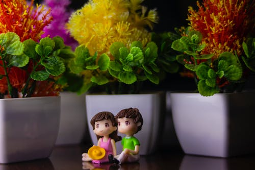 Cute couple of boy and girl figurines placed on dark table near white flowerpots with flowers and green leaves in room
