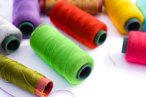 Close Up Photo Of Assorted Sewing Threads In Spools