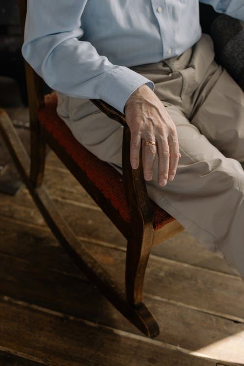 Man in Dress Shirt and Beige Pants Sitting on Brown Wooden Armchair