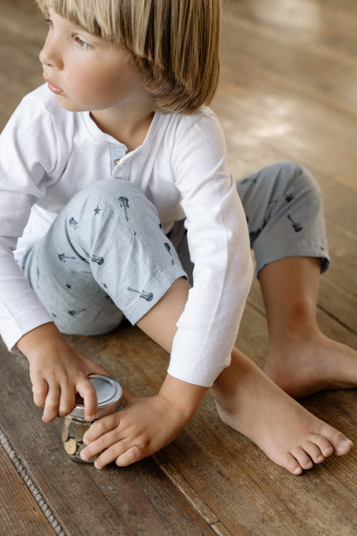 Boy in White Long Sleeve Shirt and Gray Pants Sitting on Brown Floor