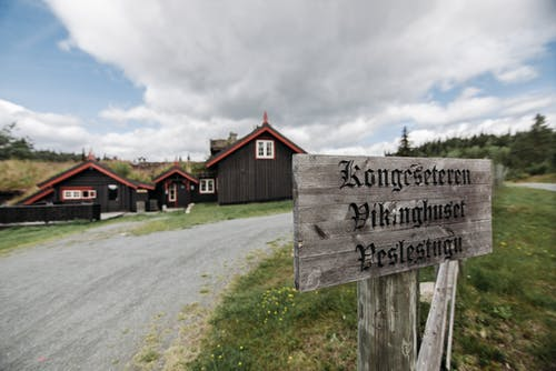 Wooden Signage with Engraved Titles Near Dark Gray Houses