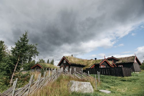 Brown Wooden House on Green Grass Field Under Gray Clouds