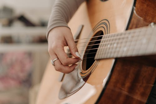 Close-Up Shot of a Person Playing Guitar