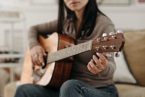 Woman Tuning a Guitar