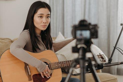 Woman Looking on Digital Camera Holding Guitar