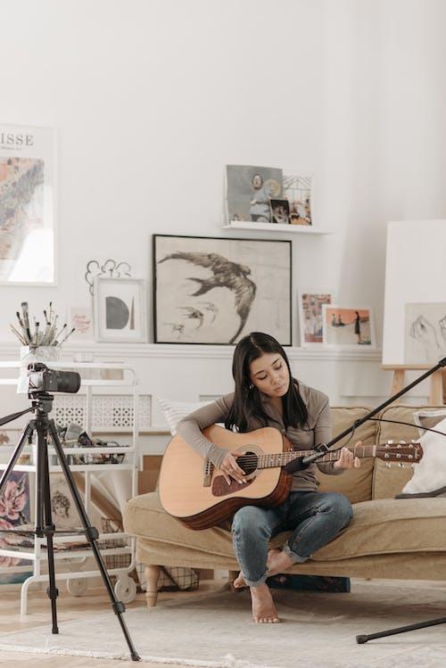 Woman Sitting on Brown Sofa Playing Guitar