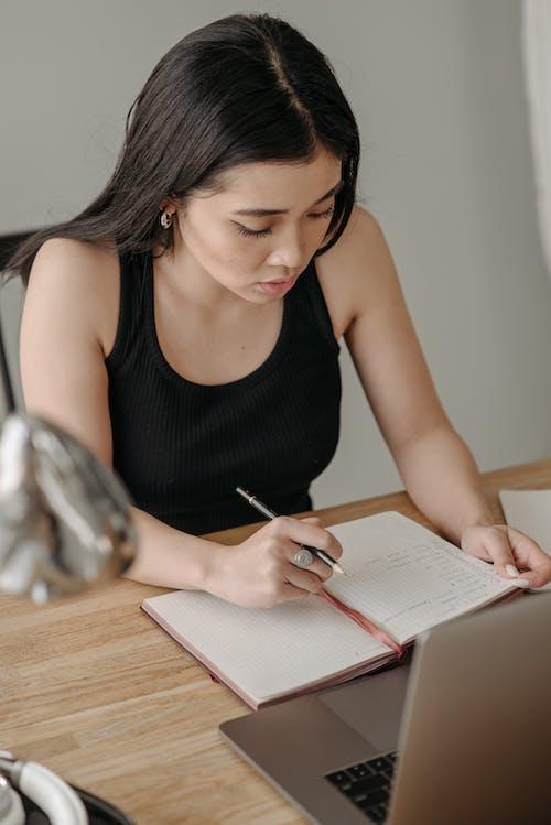 Woman in Black Tank Top Writing