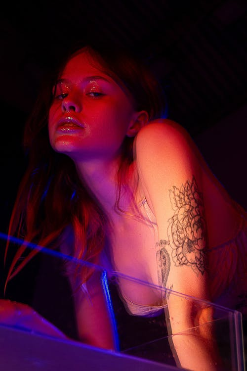 Confident young female in bra with makeup and tattoos on hand near glass container with liquid looking at camera in dark room with neon lights