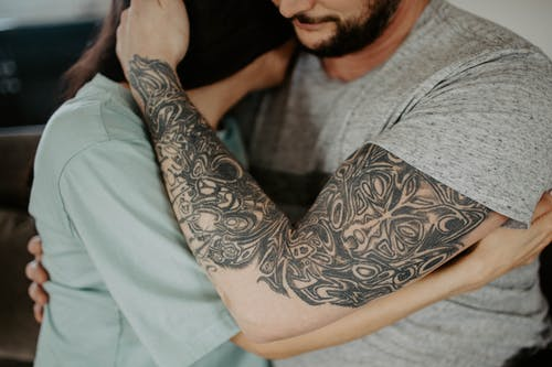 Man in Gray Crew Neck Shirt With Black Floral Tattoo on Arm