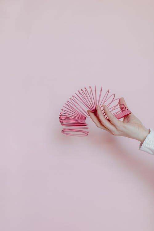 Person in White Long Sleeve Shirt Holding Pink Hand Fan