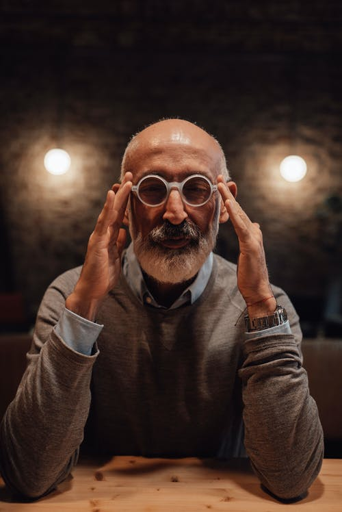 Serious mature male with gray beard touching trims of eyeglasses while sitting at wooden table in room with glowing lamps