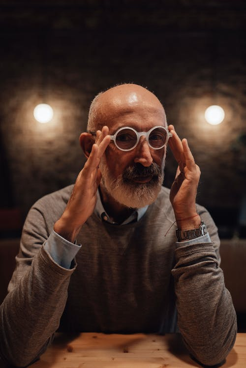 Mature male with gray beard wearing elegant outfit touching trims of eyeglasses while sitting at wooden table and looking at camera