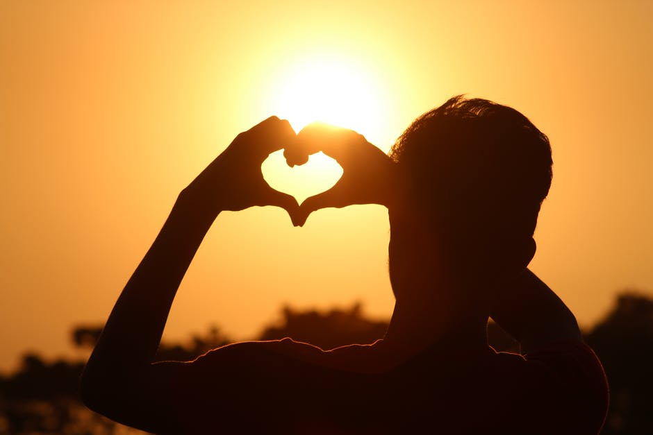 Silhouette photo of man doing heart sign during golden hour