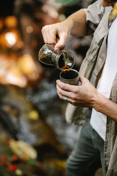 Crop male camper pouring coffee into mug in forest