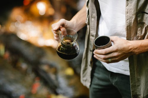 Crop anonymous male camper pouring freshly brewed coffee from chemex coffeemaker into metal mug while resting in autumn forest during trekking