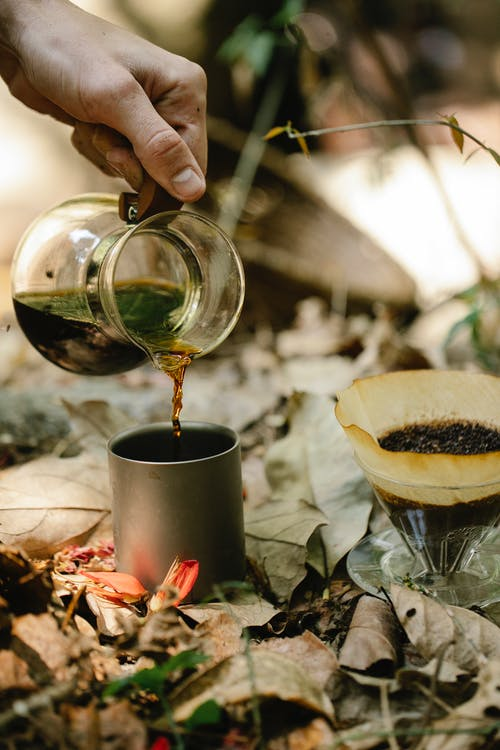 Crop unrecognizable male hiker pouring fresh hot coffee from chemex into metal mug placed on ground covered with dry fallen leaves at campsite