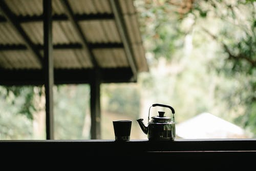 Kettle and glass of coffee on veranda