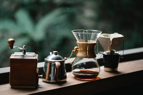 Chemex coffeemaker with cup placed on terrace with metal kettle and hand grinder