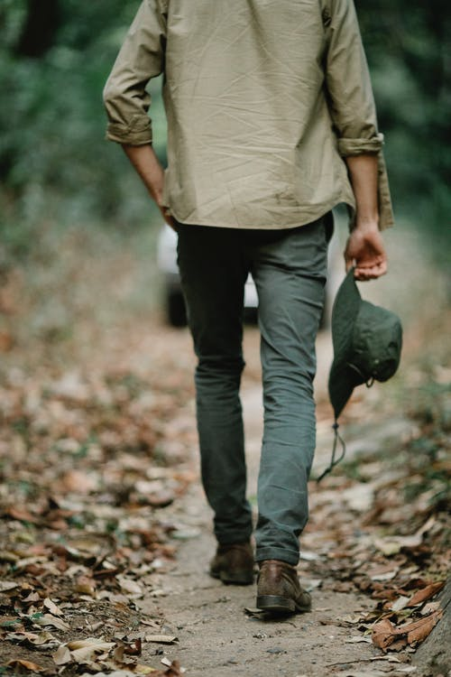 Unrecognizable guy walking in autumn forest during hiking trip
