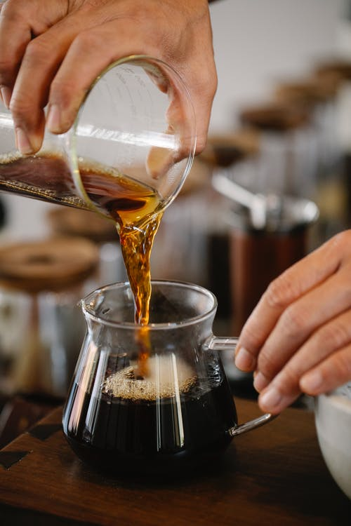 Crop unrecognizable male barista pouring freshly brewed aromatic coffee from glass measuring pitcher into hot at counter