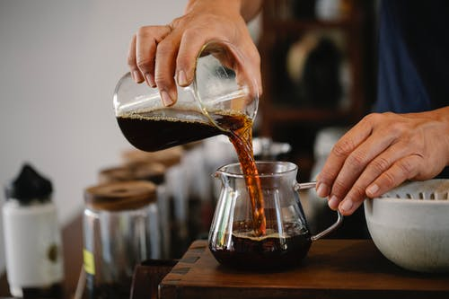 Crop faceless male worker pouring aromatic hot coffee from glass measuring pitcher into pot placed on wooden counter in cafe