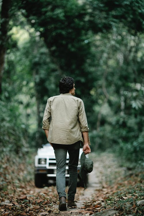 Back view of unrecognizable male traveler with dark hair in casual outfit walking in forest amidst lush green trees towards modern car parked on narrow road