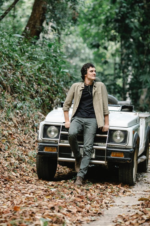 Confident young man leaning on car and looking away in autumn forest